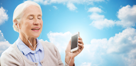 age: technology, age and people concept - happy senior woman with smartphone and earphones listening to music over blue sky and clouds background Stock Photo