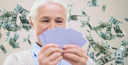 gamble: age, game, gamble, poker and people concept - close up of happy smiling senior woman playing cards over dollar money rain on background Stock Photo