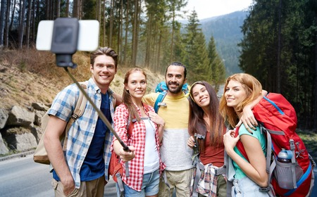 to stick: technology, travel, tourism, hike and people concept - group of smiling friends walking with backpacks taking picture by smartphone on selfie stick over woods and road background