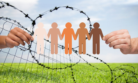 imprisonment: crime, imprisonment, refugee and humanity concept - multiracial couple hands holding chain of paper people pictogram over sky, grass and barb wire background