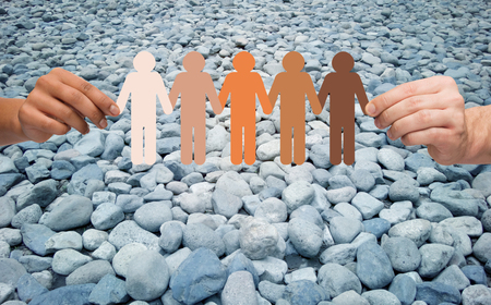 humanity: immigration, unity, population, race and humanity concept - multiracial couple hands holding chain of paper people pictogram over stones in desert background Stock Photo