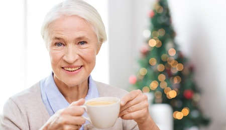 tercera edad: edad, bebida, días de fiesta, invierno y concepto de la gente - feliz mujer mayor sonriente con la taza de café en el país más de sala de estar y el fondo del árbol de navidad
