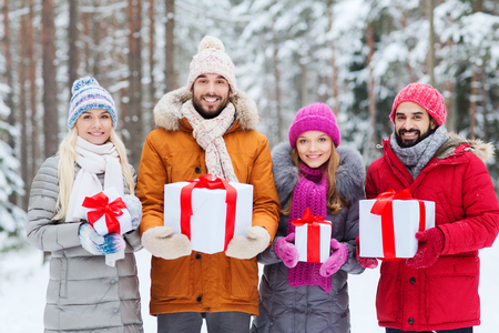 group of men: holidays, christmas, season, friendship and people concept - group of smiling friends with gift boxes in winter forest Stock Photo