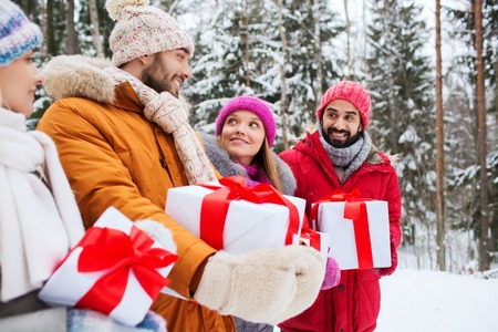 middle eastern families: holidays, christmas, season, friendship and people concept - group of smiling friends with gift boxes in winter forest Stock Photo