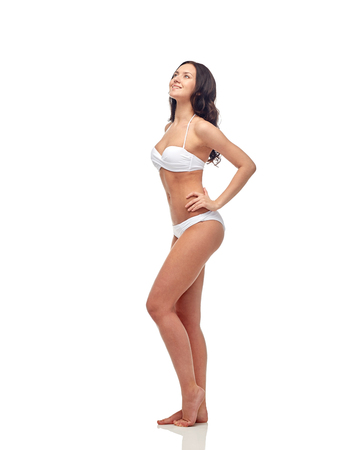 sexy woman standing: people, fashion, swimwear, summer and beach concept - happy young woman in white bikini swimsuit
