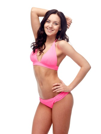 people, fashion, swimwear, summer and beach concept - happy young woman posing in pink bikini swimsuit