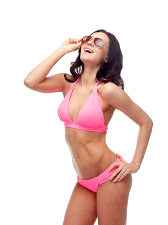 traje de baño: gente, moda, traje de baño, verano y concepto de la playa - mujer joven feliz en gafas de sol y traje de baño rosa mirando hacia arriba y riendo