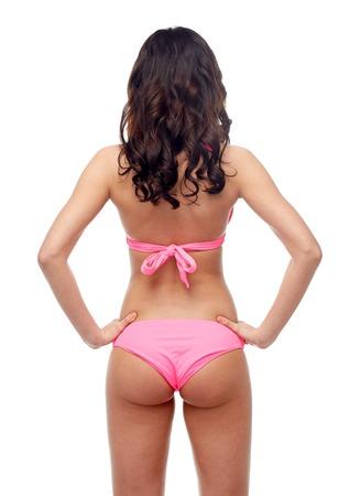 culo donna: persone, moda, costumi da bagno, spiaggia d'estate e concetto di bellezza - giovane donna in rosa costume bikini dalla parte posteriore