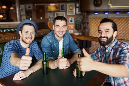 人、レジャー、友情、ジェスチャーや独身パーティーのコンセプト - 幸せな男友達びん詰めにされたビールを飲むとで親指を現してバーやパブ