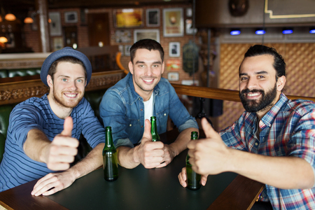single beer bottle: people, leisure, friendship, gesture and bachelor party concept - happy male friends drinking bottled beer and showing thumbs up at bar or pub Stock Photo