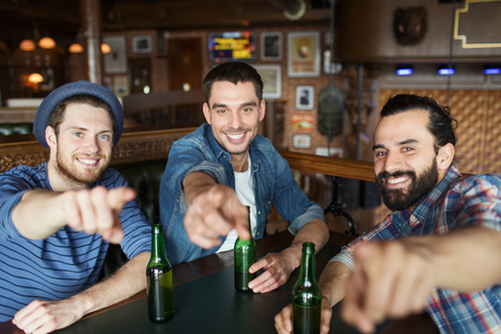 bachelor: people, leisure, friendship and bachelor party concept - happy male friends drinking bottled beer and  and pointing on you at bar or pub Stock Photo