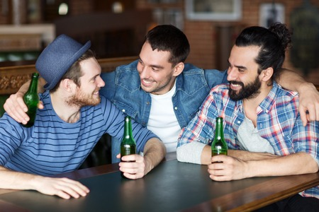 alcoholic drink: people, leisure, friendship and bachelor party concept - happy male friends drinking bottled beer and talking at bar or pub