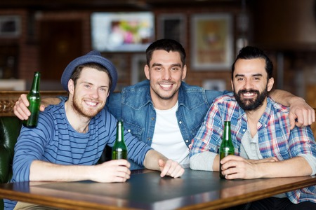 bachelor: people, leisure, friendship and bachelor party concept - happy male friends drinking bottled beer and hugging at bar or pub Stock Photo