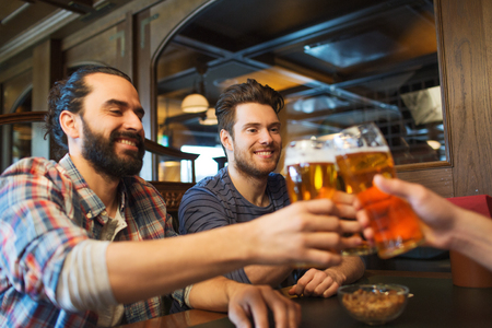 party table: people, leisure, friendship, bachelor party and celebration concept - happy male friends drinking beer and clinking glasses at bar or pub
