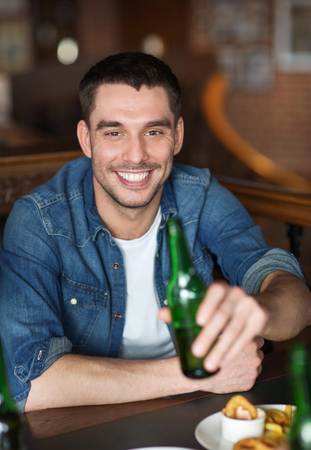 bachelor: people, leisure, celebration and bachelor party concept - happy young man drinking beer at bar or pub Stock Photo