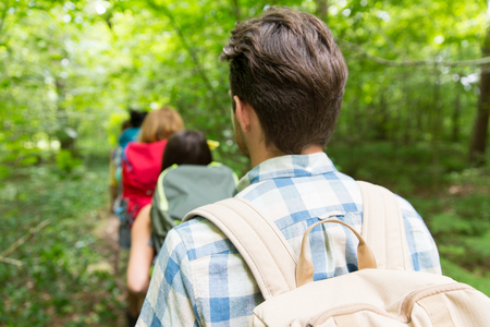 hiking: adventure, travel, tourism, hike and people concept - close up of friends walking with backpacks in woods from back Stock Photo