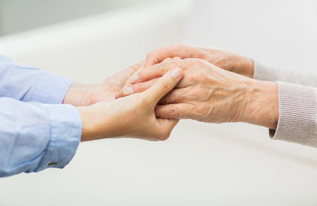 help: people, age, family, care and support concept - close up of senior and young woman  holding hands