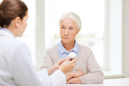 doctor with pills: medicine, age, health care and people concept - doctor showing pills to senior woman at hospital Stock Photo