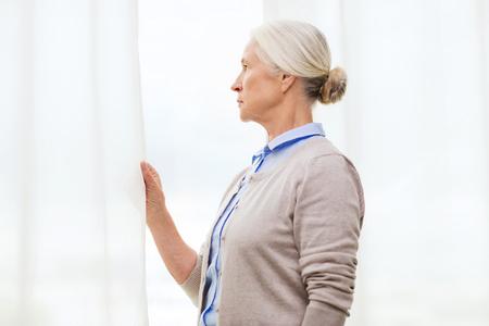 soledad: la edad, la soledad y la gente concepto - mujer mayor sola mirando por la ventana en su casa Foto de archivo