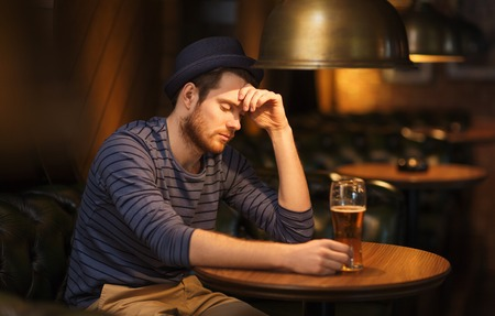 pubs: people, loneliness, alcohol and lifestyle concept - unhappy single young man in hat drinking beer at bar or pub