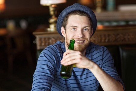 glass bottle: people, leisure, celebration and bachelor party concept - happy young man drinking beer at bar or pub Stock Photo