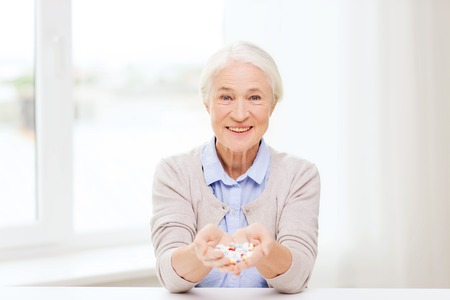 ancianos felices: age, medicine, health care and people concept - happy senior woman with pills at home or hospital office Foto de archivo