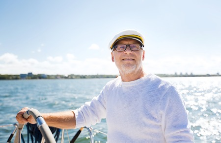 helm: sailing, age, tourism, travel and people concept - happy senior man in captain hat on steering wheel and navigating sail boat or yacht floating in sea