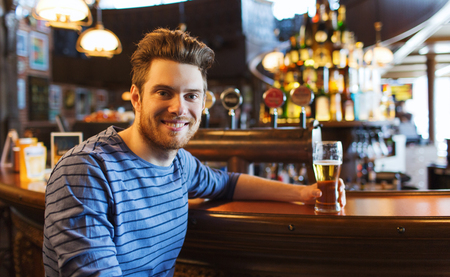 alcoholic drink: people, drinks, alcohol and leisure concept - happy young man drinking beer at bar or pub Stock Photo