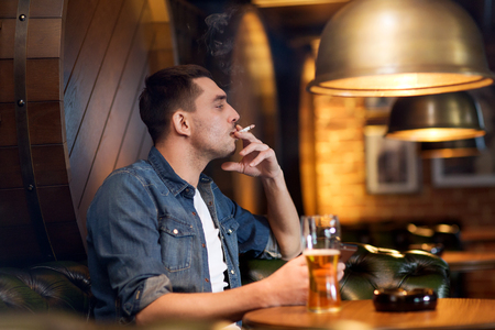 pubs: people and bad habits concept - man drinking beer and smoking cigarette at bar or pub