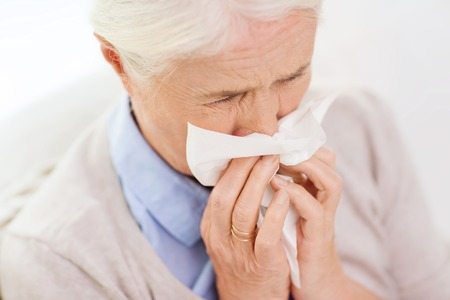 sick person: health care, flu, hygiene, age and people concept - sick senior woman blowing nose to paper napkin at home Stock Photo