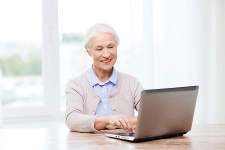 tercera edad: la tecnología, la edad y las personas concepto - mujer mayor feliz con el ordenador portátil en casa