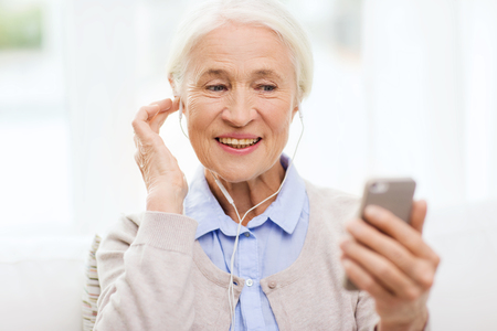 technology, age and people concept - happy senior woman with smartphone and earphones listening to music at home Stock Photo