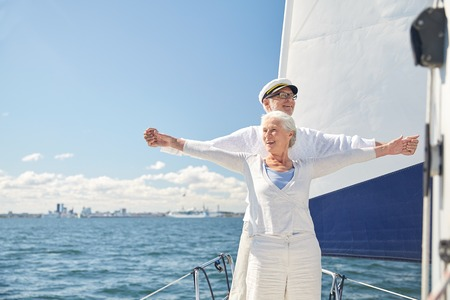sail: sailing, age, tourism, travel and people concept - happy senior couple enjoying freedom on sail boat or yacht deck floating in sea