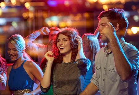 パーティ、休暇、お祝い、ナイトライフ、人コンセプト - 夜のクラブで踊る幸せな友人のグループ