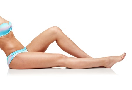 beautiful body: people, fashion, swimwear, summer and beach concept - close up of woman sunbathing in bikini swimsuit Stock Photo
