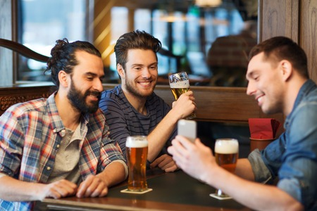showing: people, men, leisure, friendship and technology concept - happy male friends with smartphone drinking beer at bar or pub