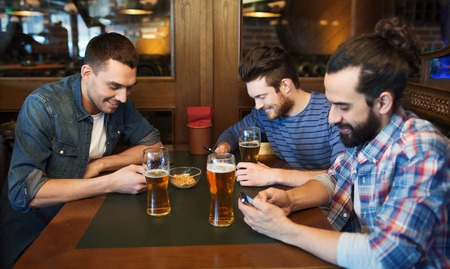 bars: people, men, leisure, friendship and technology concept - male friends with smartphones drinking beer at bar or pub