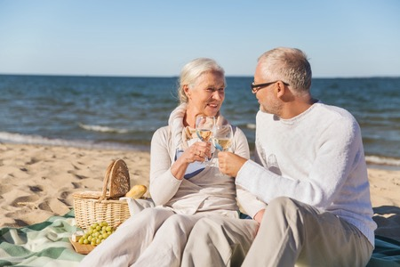 family, age, travel, tourism and people concept - happy senior couple having picnic and talking on summer beach Stock Photo