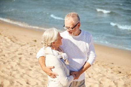 ancianos caminando: familiar, la edad, los viajes, el turismo y el concepto de la gente - feliz pareja de alto nivel que abrazan en la playa del verano Foto de archivo