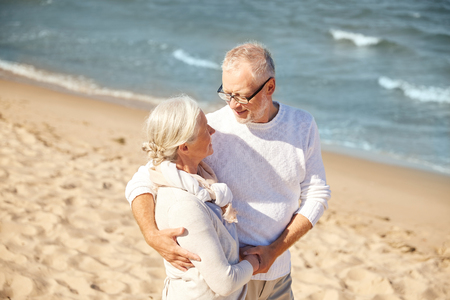 old couple walking: family, age, travel, tourism and people concept - happy senior couple hugging on summer beach