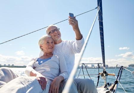 セーリング、技術、観光、旅行、人々 の概念 - 帆の海に浮かぶボートやヨットのデッキでスマート フォンで selfie を取って幸せな先輩カップル
