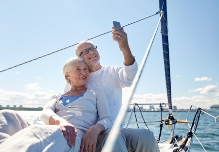 person traveling: vela, la tecnología, el turismo, los viajes y el concepto de la gente - feliz pareja senior teniendo selfie con smartphone en barco de vela o de la cubierta del yate flotando en el mar Foto de archivo