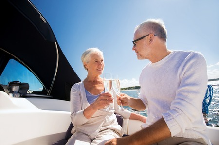 clinking: sailing, age, travel, holidays and people concept - happy senior couple clinking champagne glasses on sail boat or yacht deck floating in sea Stock Photo