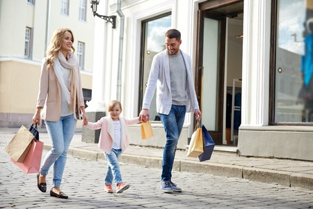 판매, 소비 사람들 개념 - 도시에 작은 아이 쇼핑 가방과 함께 행복한 가족