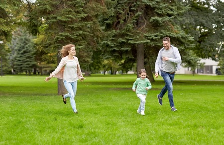 leisure game: family, parenthood, leisure and people concept - happy mother, father and little girl running and playing catch game in summer park Stock Photo