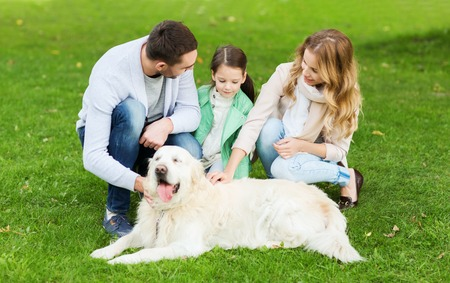 family in park: family, pet, domestic animal and people concept - happy family with labrador retriever dog on walk in summer park Stock Photo
