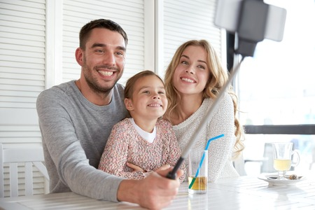 self portrait: family, parenthood, technology and people concept - happy mother, father and little girl having dinner and taking picture by smartphone selfie stick at restaurant Stock Photo