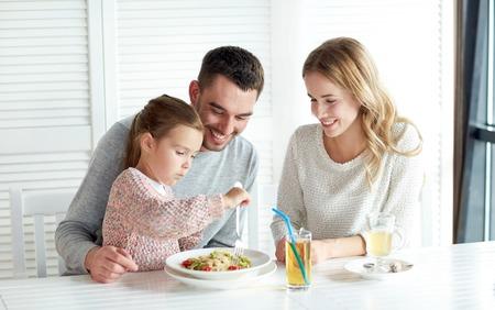 Familie, ouderschap, voedsel en mensen concept - gelukkige moeder, vader en meisje eet pasta voor het diner in het restaurant of cafe Stockfoto - 48683071