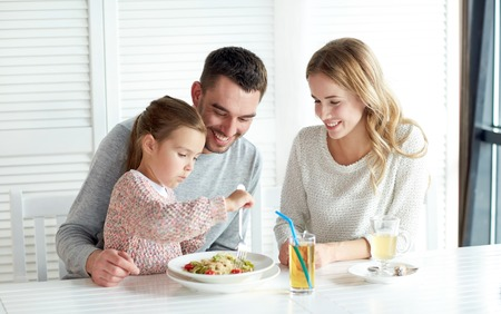 family, parenthood, food and people concept - happy mother, father and little girl eating pasta for dinner at restaurant or cafe Foto de archivo