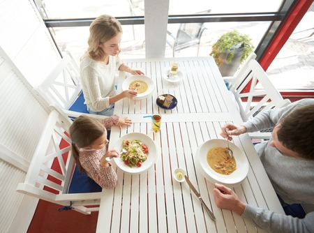 a little dinner: family, parenthood, food and people concept - happy mother, father and little girl eating soup and pasta for dinner at restaurant or cafe Stock Photo
